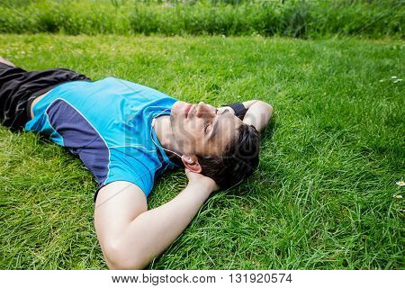 Sport fitness man relaxing listening to music after training outdoor in a city park . Young male athlete resting relaxing lying on grass after running and training exercise outside in summer. poster