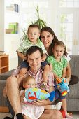 stock photo of nuclear family  - Portrait of happy family with three children at home - JPG