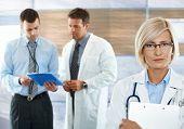 Trabajadores de la salud en el hospital corredor doctora frente mirando a cámara.