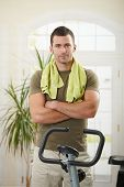 Personal trainer wearing sportswear and towel standing in living room at home with training bike, sm
