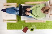 Woman typing on laptop keyboard sitting in armchair with legs crossed on footboard in high angle vie