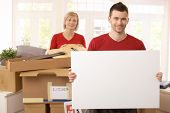 Smiling couple surrounded with boxes in new house, copyspace on blank poster.