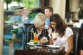 image of mobile-phone  - Young women sitting in cafe having sweets - JPG