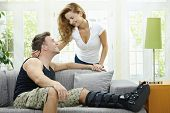 Amo o casal em casa. Homem descansa sua perna quebrada em sofá, sua namorada, abraçando-o por trás.
