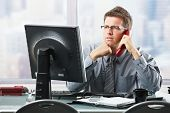 Focused businessman listening to explanation of computer report on landline phone looking at screen