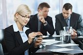 Smiling businesswoman using smartphone at office meeting with colleagues in background.?