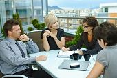 Group of young business people sitting around table on office terrace outdoor, talking and working t