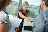 Successful job interview - happy employee shaking hands, smiling. Focus places on questionnarie in f