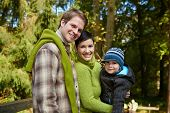 stock photo of nuclear family  - Portrait of happy family of three smiling at camera on sunny day in park - JPG