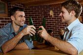 Two men drinking beer in bar, clinking bottles, smiling, women talking in background.?