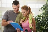 Young woman checking training plan with her personal trainer at home.