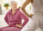 Elderly woman looking at personal trainer demonstrating exercise.?