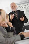 Experienced senior executive explaining work to colleagues, gesturing, smiling, standing at whiteboard.?