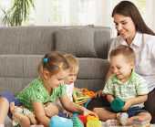 Happy mother and 3 children sitting on floor at home playing together smiling.?