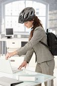 Young attractive businesswoman leaving office by bike, shutting down her laptop, wearing helmet and backpack.?
