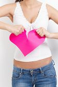 Angry lovelorn young woman tearing pink paper heart apart.?