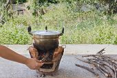 Постер, плакат: Hand Refill Twig To Fire Stove With Old Aluminium Pot dry Limb Pile For Folk Cooking Way
