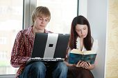 Young stylish teens home with laptop