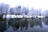 stock photo of covered bridge  - beautiful view across the lake in snow covered landscape.