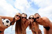 Постер, плакат: Веселые молодые люди играть в волейбол на пляже Великий летних каникул