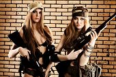 Two sexy women in military uniform posing against brick background.