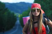 Pretty young woman tourist hitchhiking along a road. poster