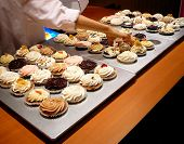 Baker Reaches For Cupcake In Gourmet Bakery