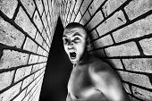 stock photo of skinhead  - Portrait of a handsome muscular man posing over black background and brick wall - JPG