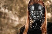 Portrait of an artistic woman painted with black color and spangled. Body painting project. Jewellery.
