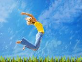 Beautiful blond girl jumps over green grass