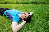 Sport fitness man relaxing listening to music after training outdoor in a city park . Young male athlete resting relaxing lying on grass after running and training exercise outside in summer. t-shirt