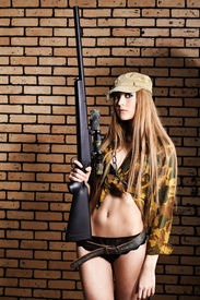 pic of girls guns  - Shot of a sexy woman in military uniform posing against brick background - JPG