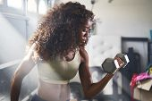 strong african american woman doing weight lifting at home inside garage poster