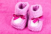 bright baby booties on pink background
