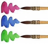 3 brushes with different colors of paint, isolated on white background