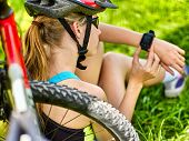 Woman traveling bicycle in summer park. Bicyclist girl watch on smart watch. Girl counts pulse after poster
