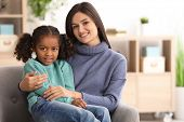 Young woman with little African-American girl indoors. Child adoption poster