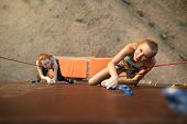 Strong Woman And Business Concept. Top View Of Two Young Climbers Approaching To Finishing Point On  poster