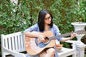 Music Concepts. Asian Girls Playing Guitar. Asian Women Relaxing With Music. Asian Women Have A Happ poster