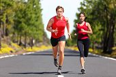 Running fitness couple of runners doing sport on road outdoor. Active living man and woman jogging t poster
