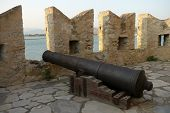 stock photo of trebuchet  - This picture shows an old cannon pointing from a castle wall out to sea - JPG