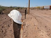 A Construction Hard Hat Abandoned On A Post Next To Railroad Tracks In A Remote Area Of Arizona. The poster