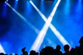 Concert crowd attending a concert, people silhouettes are visible, backlit by stage lights. Raised h poster