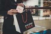 Close Up Of Female Hands Holding Beautiful Box And Shopping Bag With Printed Written Words Black Fri poster