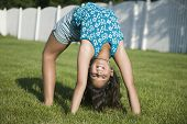Hispanic girl doing back bend on grass