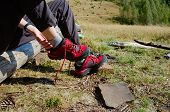 Young Traveller Girl Taking Hiking Shoes Off On Camping During Hiking In Mountains. Hiker Shoes Off  poster