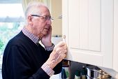 Forgetful Senior Man With Dementia Looking In Cupboard At Home poster