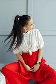 Gorgeous Brunette Woman In Red Fashion Pans And White Shirt Moving Hair. Fashion Young Woman Indoor  poster