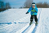Cute little boy skiing downhill