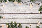 Christmas Lights Bulb And Pine Leaves Decoration On White Wood Plank, Frame Border Design. Merry Chr poster